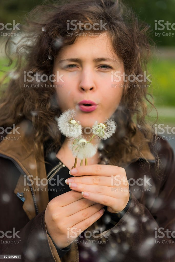 Young woman girl holding and blowing three dandelions stock photo