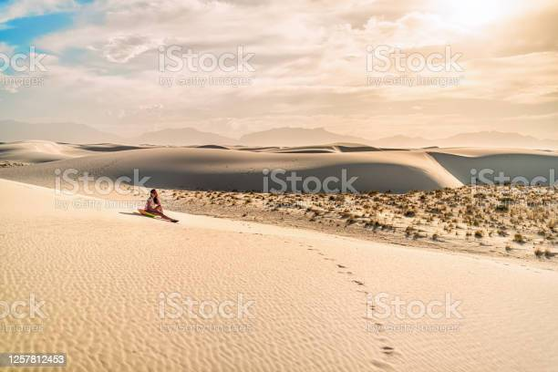 Photo of Young woman girl on sand in white sands dunes national monument in New Mexico sitting on disk sled for sliding down hill during vintage tone sunset