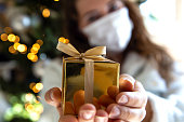 istock Young woman gives golden gift box wearing a protective Face maks for Covid-19, present and Coronavirus concept. social distance 1279859702
