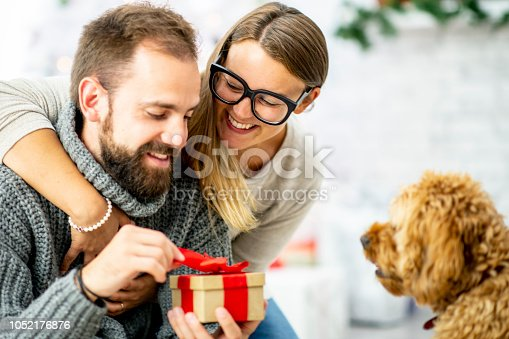 A caucasian woman smiles as she puts her arm around her boyfriend's shoulder and hands him a wrapped gift with her other. A dog watches them while sitting next to them.
