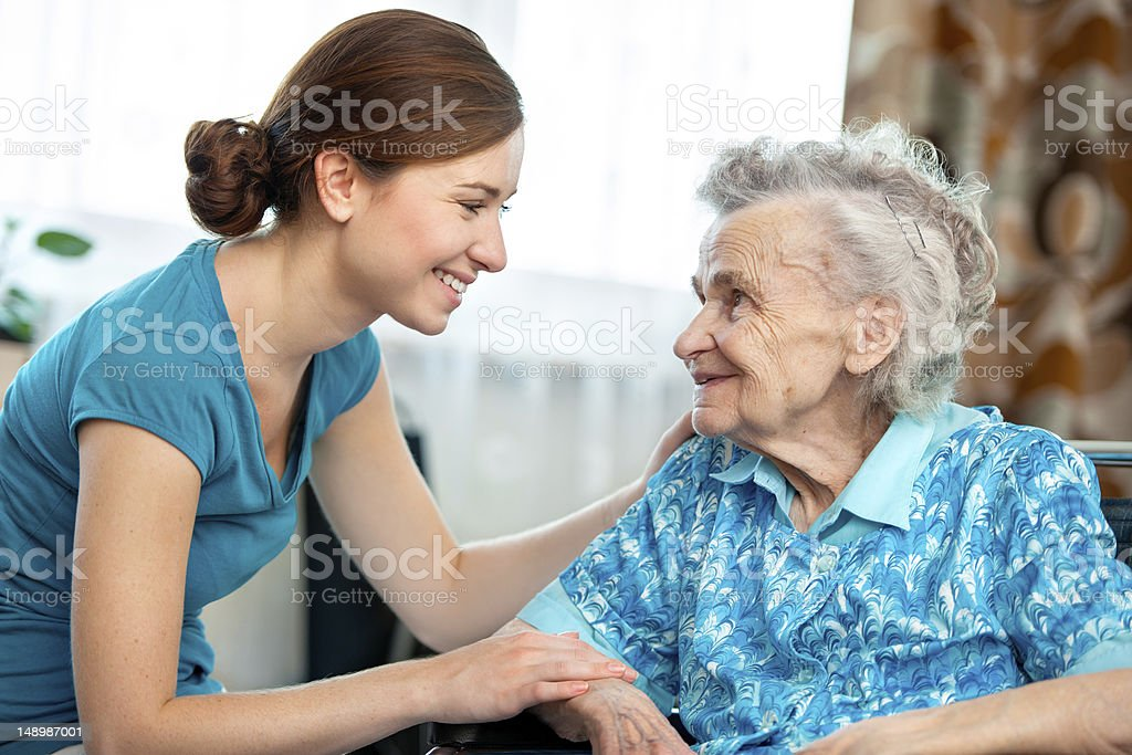 Young woman giving an elderly woman a friendly greeting royalty-free stock photo