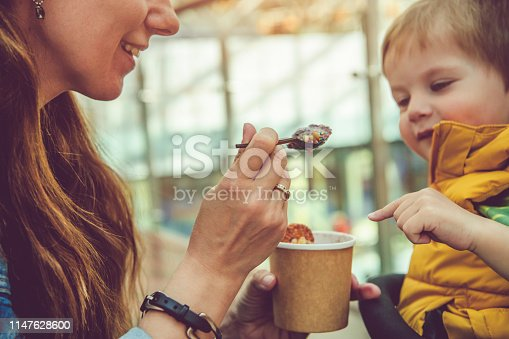 958492394 istock photo Young woman giving his son healthy rolled ice-cream or yogurt with fruits or berries, cookies, candy and mint 1147628600
