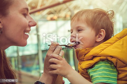 958492394 istock photo Young woman giving his son healthy rolled ice-cream or yogurt with fruits or berries, cookies, candy and mint 1147628612