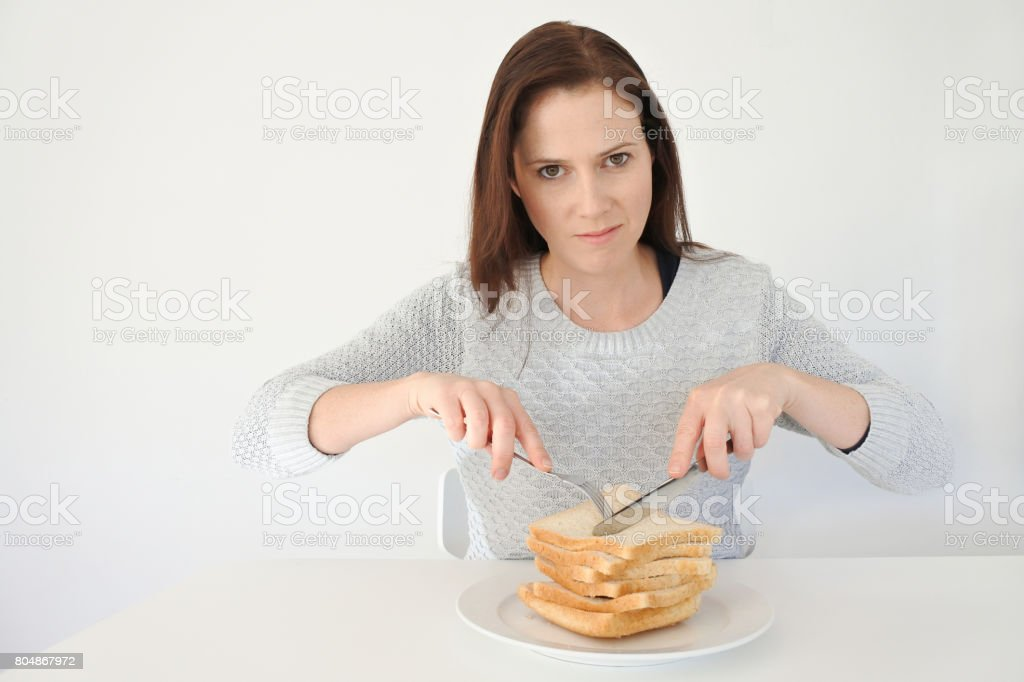 Young woman giving in to her urge and craving to Carbohydrates stock photo