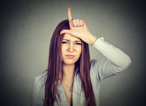 young woman giving loser sign on forehead Closeup portrait young woman giving loser sign on forehead, looking at you with disgust on face isolated on gray wall background. Negative human emotion facial expression antagonize stock pictures, royalty-free photos & images
