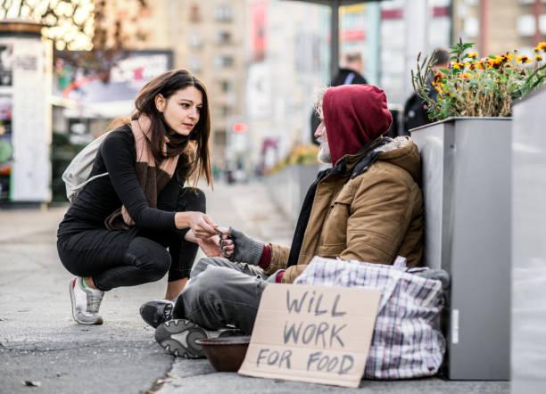 jovem mulher dando dinheiro ao mendigo sem teto na cidade. - sem teto - fotografias e filmes do acervo