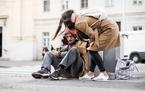Young woman giving money to homeless beggar man sitting in city. A young woman giving money to homeless beggar man sitting outdoors in city. homelessness stock pictures, royalty-free photos & images