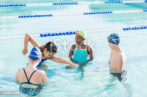 A young woman, 19 years old, Chinese ethnicity, standing in a swimming pool with a multi-ethnic group of girls and a boy, giving them a swimming lesson on freestyle. The children are 10 to 12 years old.