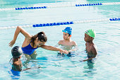 A young woman, 19 years old, Chinese ethnicity, standing in a swimming pool with a multi-ethnic group of boy, giving them a swimming lesson on freestyle. The children are 9 and 10 years old.
