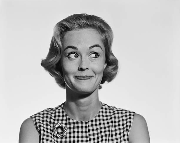 młoda kobieta uśmiechając się glancing na boki, - archiwalny zdjęcia i obrazy z banku zdjęć