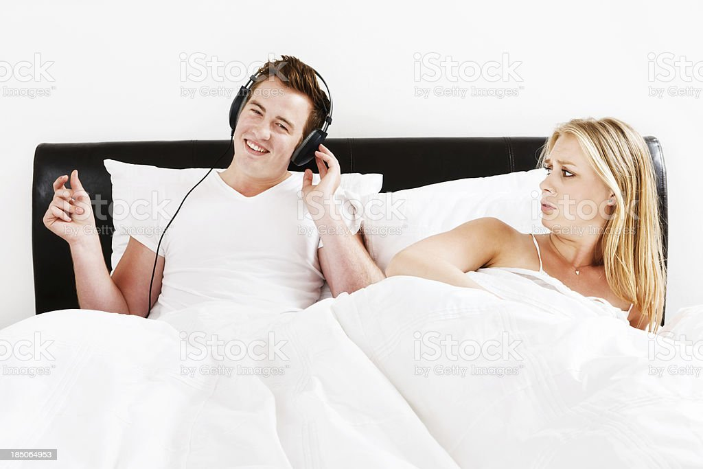 Young woman glares at partner listening to music in bed royalty-free stock photo