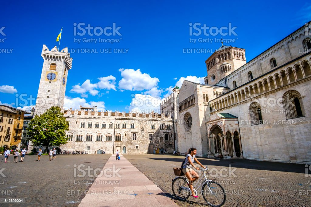 young woman go in bicycle in Piazza Duomo Trento Travel by bicycle in Italy cultural trip in Italy stock photo