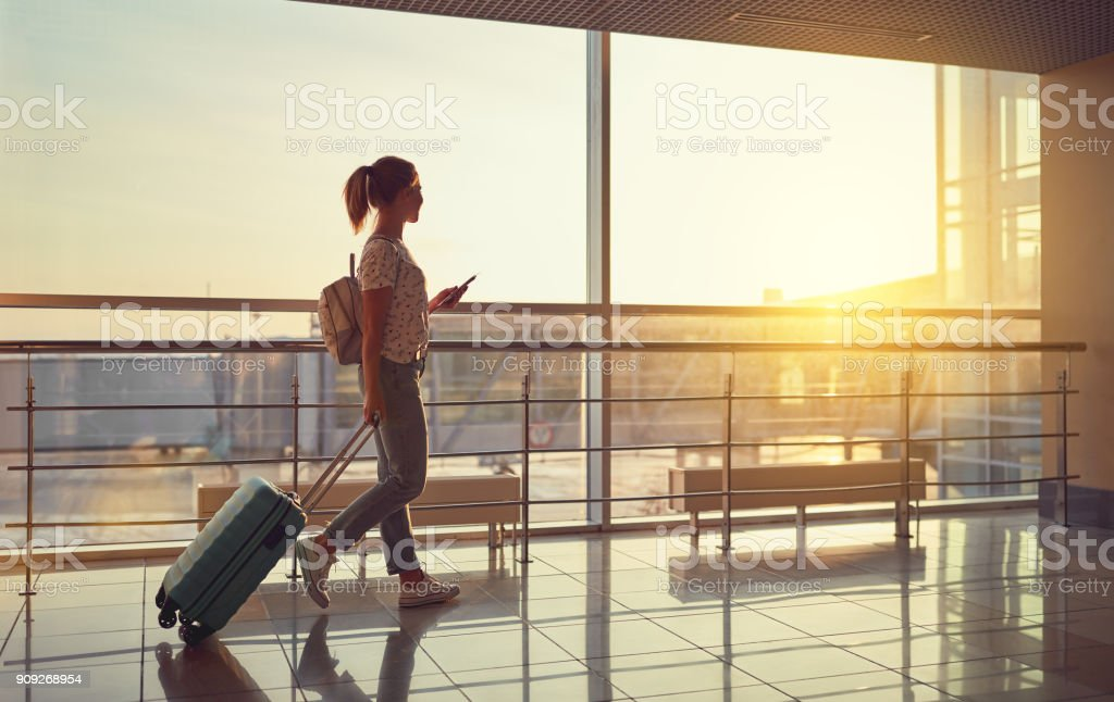 young woman goes  at airport at window with suitcase waiting for plane royalty-free stock photo