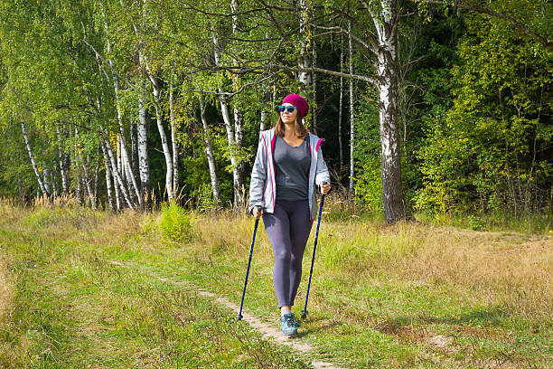 Young woman goes Nordic walking Young woman goes Nordic walking outdoors nordic walking stock pictures, royalty-free photos & images