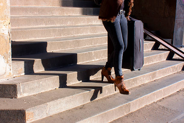Young woman going down the city stairs carrying a suitcase Belgrade, Serbia - November 20, 2016: Young woman in pants and high heels going down the city stairs carrying a suitcase, shot from the waist down skinny pants stock pictures, royalty-free photos & images