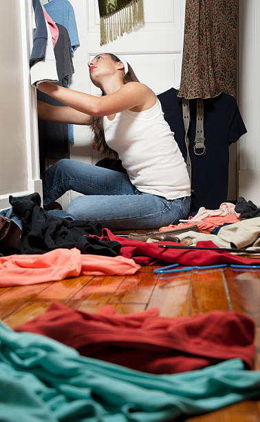 young woman going through her closet - kellyjhall stock pictures, royalty-free photos & images