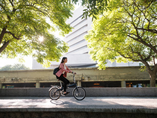 Young woman going to work by bike stock photo
