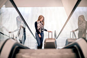 Young woman going up the escalator with luggage