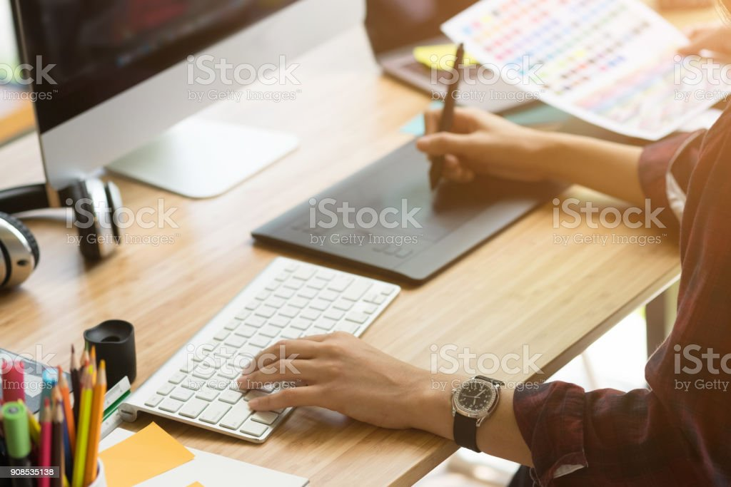 Young woman Graphic designer using interactive pen display, digital Drawing tablet and Pen on a computer. – zdjęcie