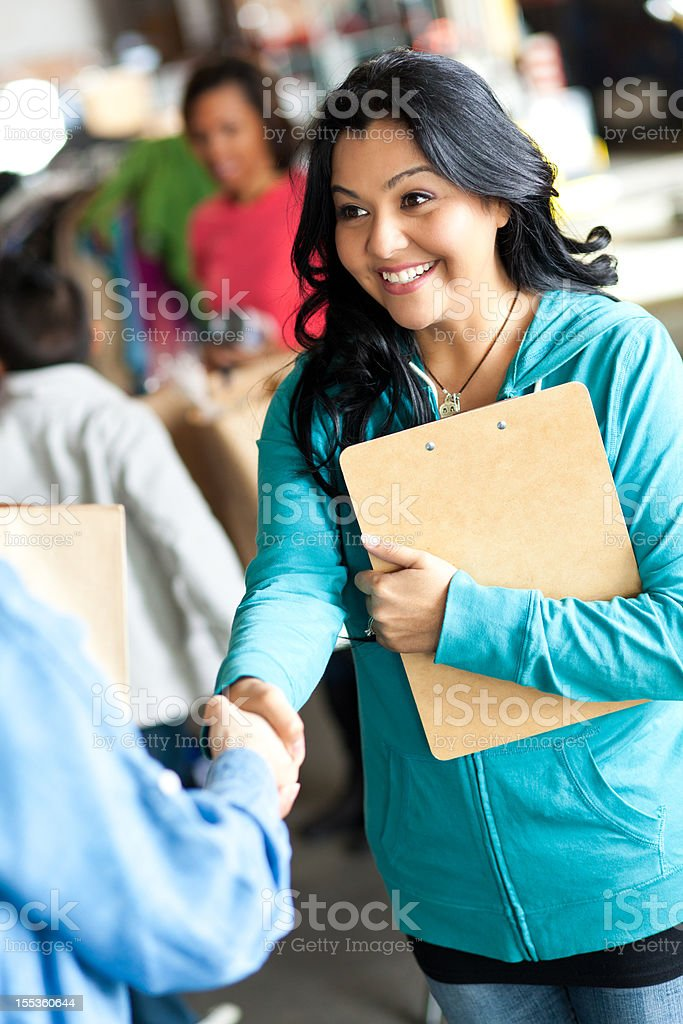 Young woman greating customer at a donation center royalty-free stock photo
