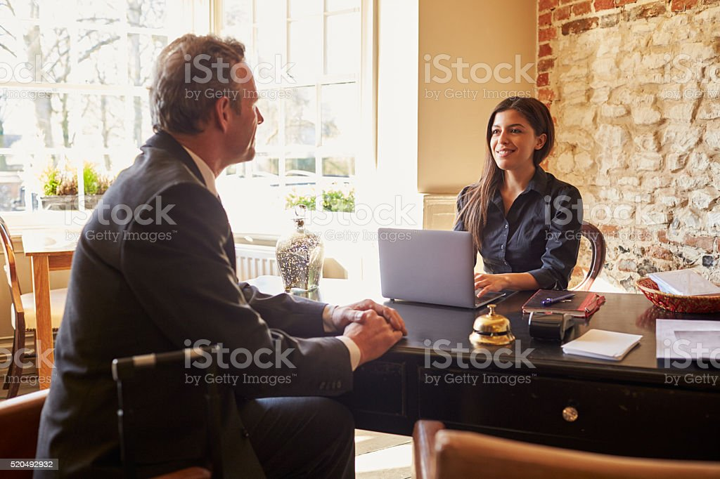 Young woman greeting a guest at the check-in desk stock photo