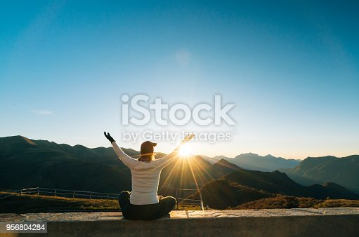 619670604 istock photo Young woman greets sunrise in mountains with arms up 956804284