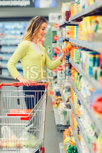 Young smiling woman groceries shopping in local supermarket. She is standing and taking box from the shelf and reading nutrition facts. With one hand she holding shopping trolley.