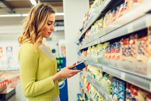young woman groceries shopping in local supermarket. - ingrediënt stockfoto's en -beelden