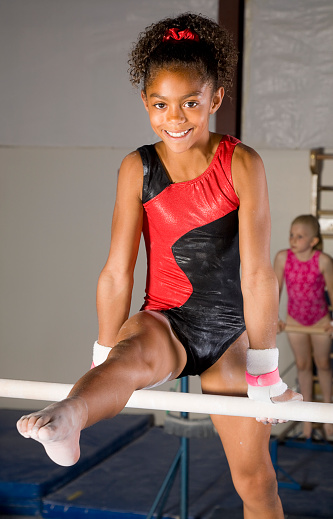 A A young gymnast balancing on the parallel bars.