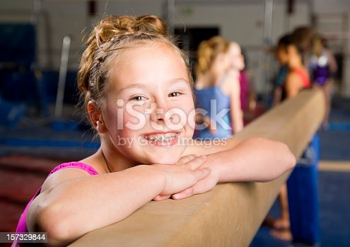 A smiling young gymnast in a gym.