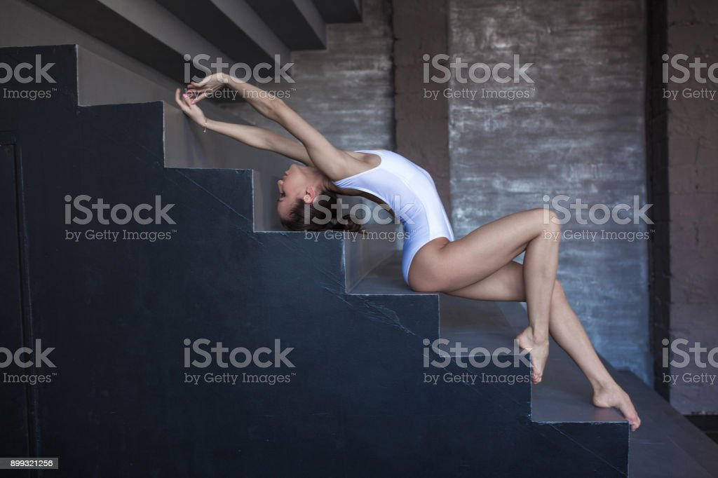 Young woman gymnast warms up in beautiful pose on the stairs. stock photo