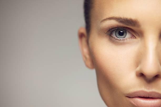 young woman half face closeup - kvinna ansikte glow bildbanksfoton och bilder