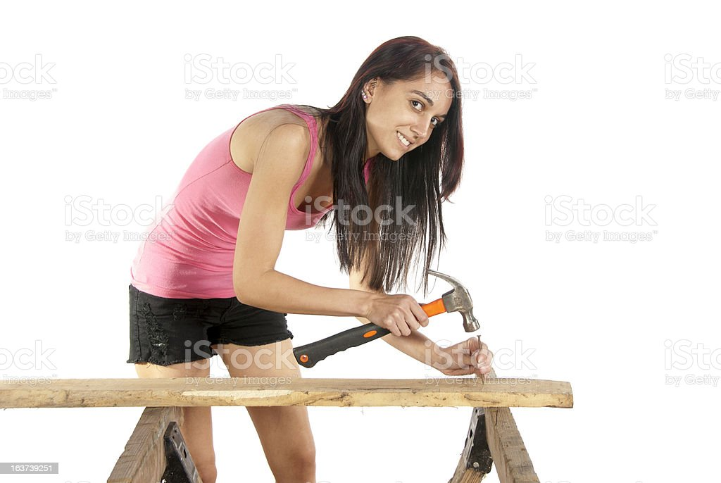 Young woman hammering nail into wood royalty-free stock photo