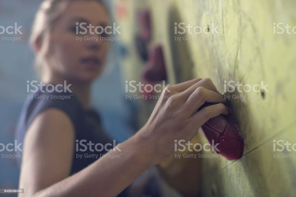 Young woman hand gripping hold on climbing wall – Foto