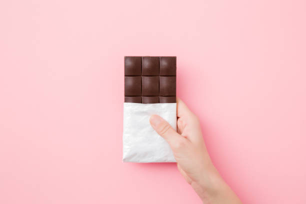 Young woman hand holding chocolate bar on light pink table background. Opened pack. Sweet snack. Closeup. Top down view. stock photo
