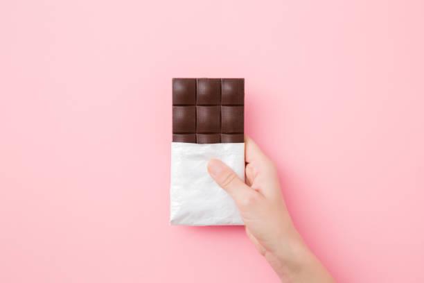 jonge vrouwenhand die chocoladestaaf op licht roze lijstachtergrond houdt. geopende verpakking. zoete snack. close-up. boven naar beneden weergave. - pure chocola stockfoto's en -beelden