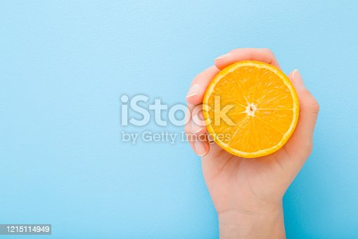 Young woman hand holding half of orange. Fresh fruit. Empty place for text on light blue table background. Pastel color. Closeup. Top down view.