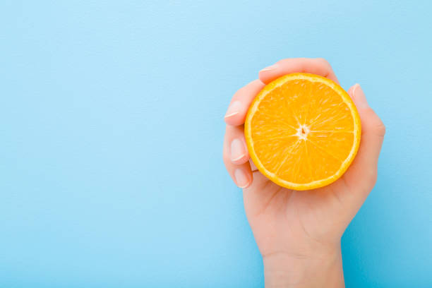 Young woman hand holding half of orange. Fresh fruit. Empty place for text on light blue table background. Pastel color. Closeup. Top down view. stock photo