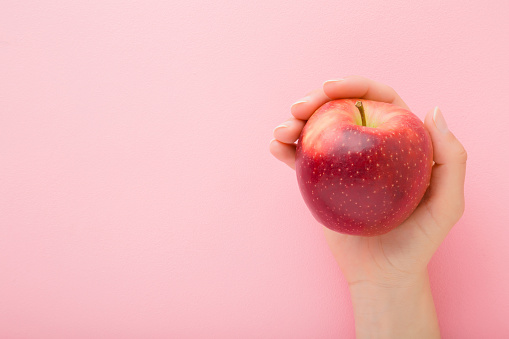 Young woman hand holding red apple on light pink table background. Fresh fruit. Pastel color. Closeup. Point of view shot. Empty place for text. Top down view.