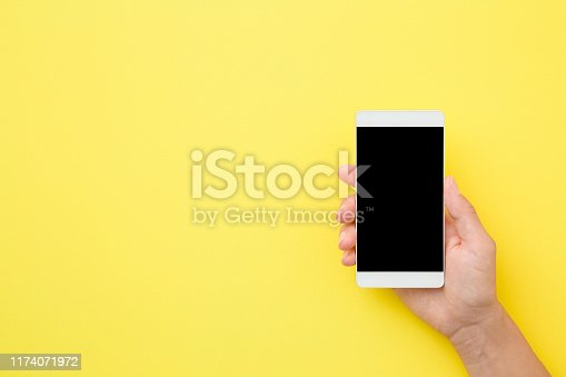 istock Young woman hand holding smartphone on yellow background. Empty place for text on black screen. Close up. Top view. 1174071972