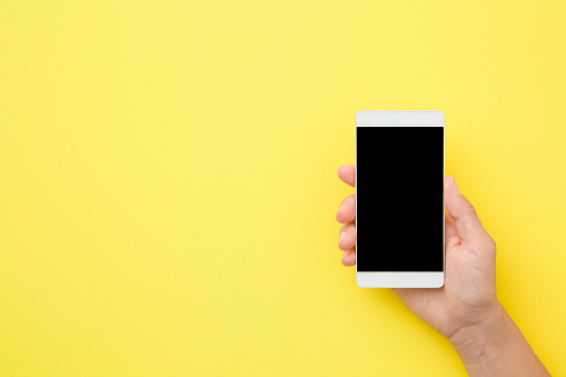 1084491176 istock photo Young woman hand holding smartphone on yellow background. Empty place for text on black screen. Close up. Top view. 1174071972