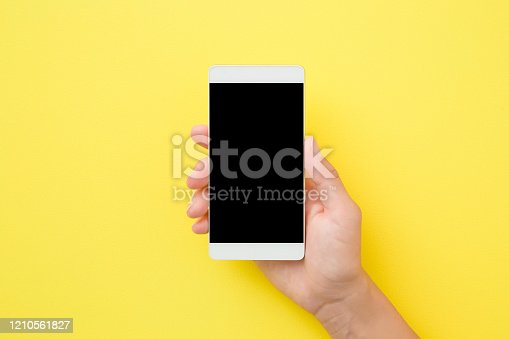 1084491176 istock photo Young woman hand holding smartphone on yellow background. Empty place for text on black screen. Closeup. Top down view. 1210561827
