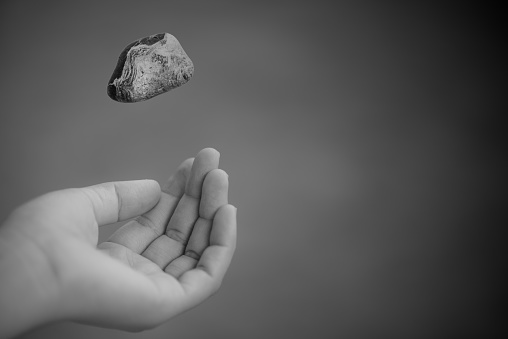 Young woman hand throwing stone