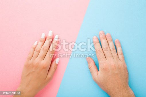 1147741037 istock photo Young woman hand with white nail polish and man hand. Light pink and blue table background. Pastel color. Closeup. Top down view. 1262873135