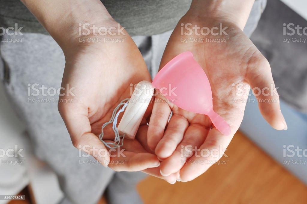 Joven manos sostener diferentes tipos de productos de higiene femenina - copa menstrual y tampones - foto de stock