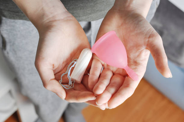 young woman hands holding different types of feminine hygiene products - menstrual cup and tampons - styles stock photos and pictures