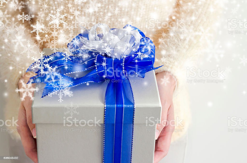 Young woman hands holding silver gift box with snowflake stock photo