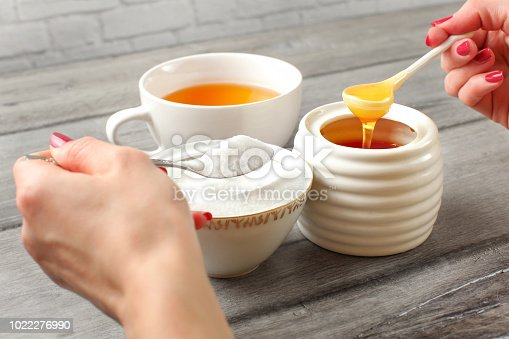istock Young woman hands holding spoon of sugar, and honey deciding what to put in tea. Refined vs natural sweetener concept. 1022276990