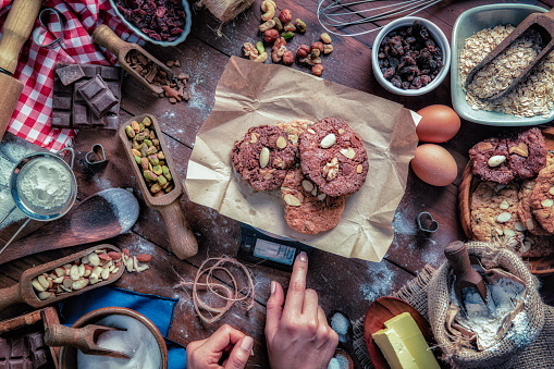 Young woman hands placing chocolate and nuts cookies on digital weight scale.