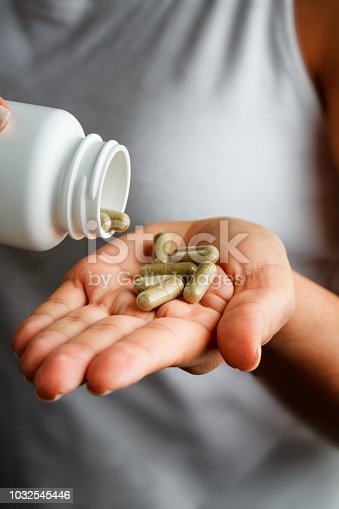 Health themes. Young woman hands with plastic bottle and alternative medicine capsules for homeopathic treatments